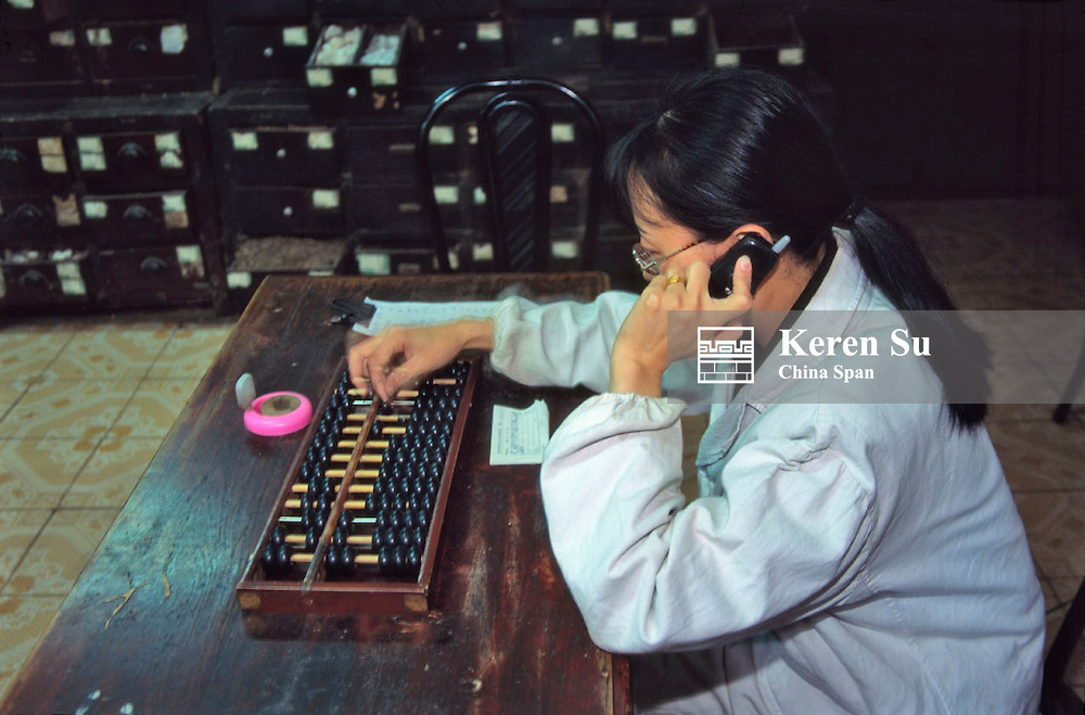 Woman using traditional abacus and modern cellular phone in Chinese medicine pharmacy, Sichuan, China