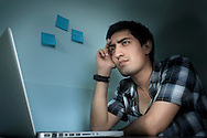 Young man deep in thought in front of a computer. The image is available for commercial licensing through Arcangel Images. ID# AA1644957 . Contact LOxArte for Fine Art Prints.