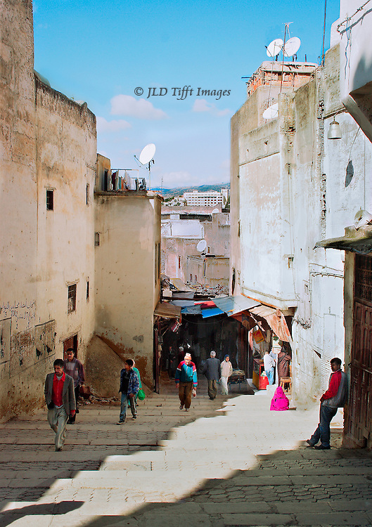View down one of the entrance streets that leads into the ancient town and medina of Fez, Morocco.  Five scattered pedestrians walk toward the camera, two away; one shopkeeper arranges his goods; one young man leans against the corner of a building in the foreground.  Bright sunlight.  Five satellite dishes visible on different rooftops of several ancient apartment buildings.   Old and new juxtaposed in comfortable coexistence.  Viewpoint slightly high so that beyond the deeply shadowed medina area at the end of the street we can see a glimpse of modern construction and blue hills beyond.  Fez lies in a bowl with hills on all sides.