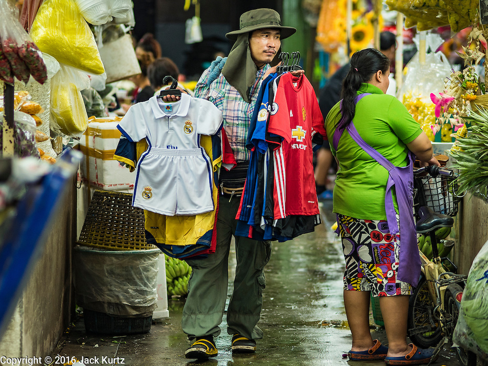 """11 AUGUST 2016 - BANGKOK, THAILAND:  A clothing vendor walks through Pak Khlong Talat selling sports themed jerseys. Pak Khlong Talat (literally """"the market at the mouth of the canal"""") is the best known flower market in Thailand. It is the largest flower market in Bangkok. Most of the shop owners in the market sell wholesale to florist shops in Bangkok or to vendors who sell flower garlands, lotus buds and other floral supplies at the entrances to temples throughout Bangkok. There is also a fruit and produce market which specializes in fresh vegetables and fruit on the site. It is one of Bangkok's busiest markets and has become a popular tourist attraction.         PHOTO BY JACK KURTZ"""