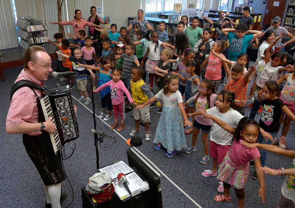 """gbs061417a/ASEC -- Mike Schneider """"Uncle Mike"""" of Clinton, Wisconsin plays polkas on his accordion to get kids dancing during and educational and musical experience to promote the summer reading program at the South Broadway Library on Wednesday, June 14, 2017. The program, Pint Size Polkas, is funded by the Friends for the Public Library. (Greg Sorber/Albuquerque Journal)"""