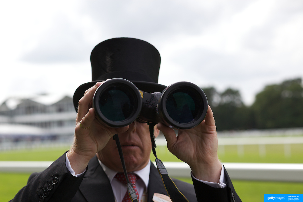 A race goer looks through a pair of binoculars during the race meeting at Royal Ascot Race Course. Royal Ascot is one of the most famous race meetings in the world, frequented by Royalty and punters from the high end of society to the normal everyday working class. Royal Ascot 2009, Ascot, UK, on Thursday, June 18, 2009. Photo Tim Clayton