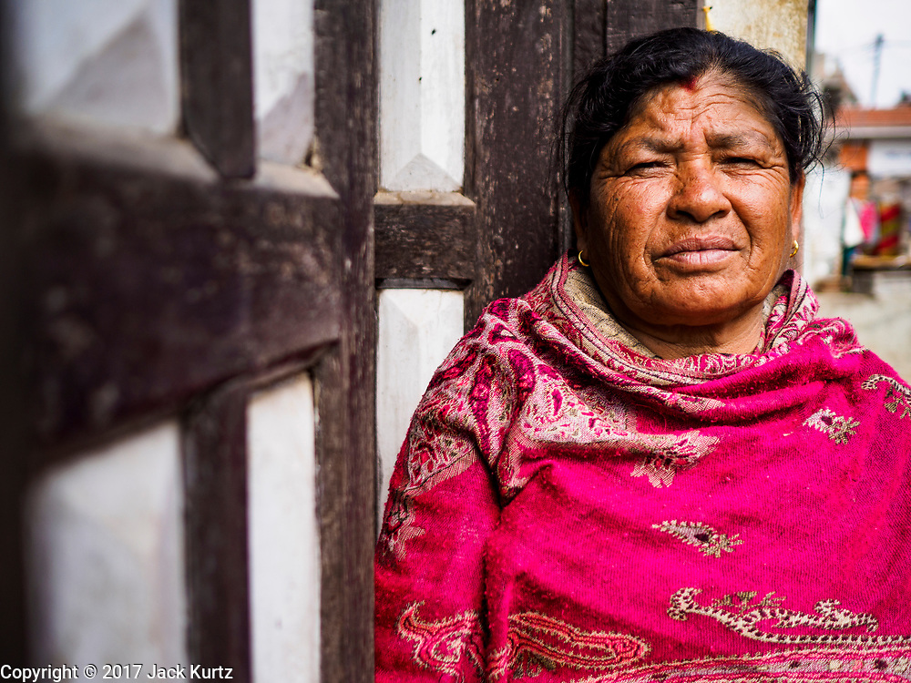 15 MARCH 2017 - BUNGAMATI, NEPAL: A woman on the front step of her home in Bungamati. Bungamati, a community of wood carvers and artisans, used to be a stop on the tourist trail of the Kathmandu valley but since the 2015 earthquake few tourists visit the community. Recovery seems to have barely begun nearly two years after the earthquake of 25 April 2015 that devastated Nepal. In some villages in the Kathmandu valley workers are working by hand to remove ruble and dig out destroyed buildings. About 9,000 people were killed and another 22,000 injured by the earthquake. The epicenter of the earthquake was east of the Gorka district.            PHOTO BY JACK KURTZ