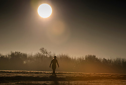 © Licensed to London News Pictures. 02/12/2019. Epsom, UK. A walker braves the cold on Epsom Downs at sunrise. A cold start for some parts of the south with temperatures just below freezing at dawn. Photo credit: Peter Macdiarmid/LNP