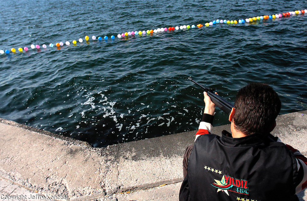 A man shoots an air rifle at balloons floating on Izmir Bay in Izmir, Turkey.
