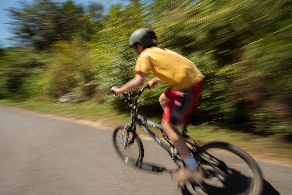 United States, Washington, Redmond, boy on bicycle on Sammamish River Ttrail  (blurred motion)