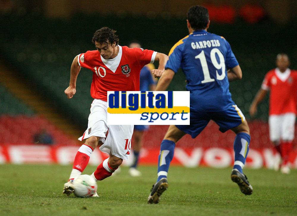 Photo: Rich Eaton.<br /> <br /> Wales v Cyprus. UEFA European Championships 2008 Qualifying. 11/10/2006. Simon Davies, left of Wales takes on Alexandros Garpozis