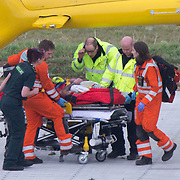 PIC BY ADAM REEVE/GEOFF ROBINSON PHOTOGRAPHY 07976 880732.<br /> <br /> Picture shows the rescue of Jim Schembri  on March 22nd near Wisbech,Cambs,after he had an accident in a tree.Mr Schembri  (on stretcher)was helped by Prince William (2nd right) and the crew of the East Anglian Air Ambulance.<br /> <br />  A former soldier has described how Prince William held his head and exchanged &ldquo;military banter&rdquo; with him for half an hour after he was knocked unconscious by a tree branch.<br /> <br /> Jim Schembri didn&rsquo;t know the Duke of Cambridge had come to his rescue when he suffered a nasty accident at work on Tuesday.<br /> <br /> The 37-year-old, who used to serve in the Light Infantry, joked that he didn&rsquo;t want William flying him to hospital in the air ambulance before realising he was already looking after him.<br /> <br /> &ldquo;I remember the helicopter landing and the doctor talking to me and someone was supporting my head,&rdquo; said Jim.<br /> <br /> &ldquo;He asked me if I was a bootneck as he had spotted a Royal Marines charity band on my arm. Then he said &lsquo;you&rsquo;ve got an ex-army air corp working on you.<br /> <br /> &ldquo;I still didn&rsquo;t twig that it was Prince William and we joked around, exchanging military banter for about half an hour.<br /> <br /> &ldquo;When they loaded me into the helicopter I said &lsquo;William had better not be flying this&rsquo; and he said &lsquo;I&rsquo;ve been holding your head for the last half an hour.&rsquo; I was totally shocked.&rdquo;<br /> <br /> Jim, who has been a tree surgeon for 14 years, had been working in a garden in Wisbech, Cambridgeshire, when the accident happened.<br /> SEE COPY CATCHLINE Former soldier helped by Will