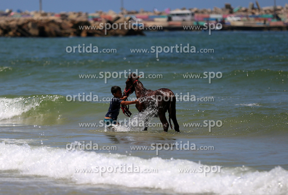 30.04.2015, Gaza city, PSE, am Strand von Gaza Stadt, im Bild ein Junge w&auml;scht sein Pferd im Meer // A Palestinian boy washes his donkey as he swims at the beach of Gaza city, Palestine on 2015/04/30. EXPA Pictures &copy; 2015, PhotoCredit: EXPA/ APAimages/ Ashraf Amra<br /> <br /> *****ATTENTION - for AUT, GER, SUI, ITA, POL, CRO, SRB only*****