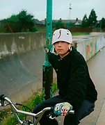 Boy sitting on his BMX, holding onto a lamp post, Romford Skate Park, UK 1990's