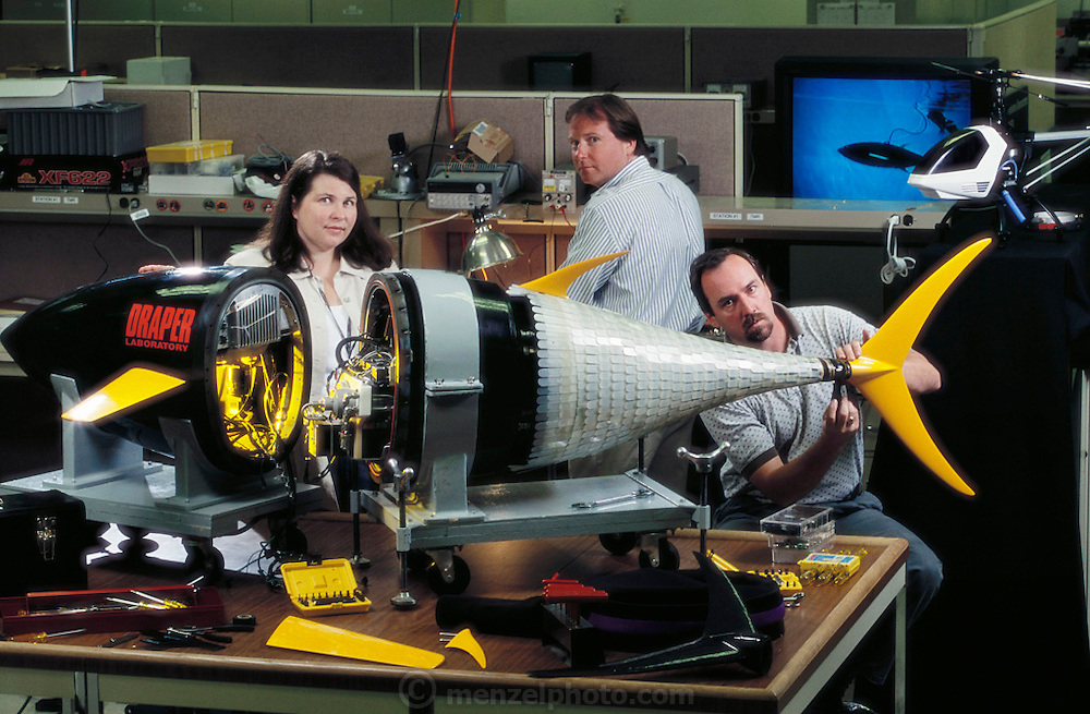 Group Leader Jamie Anderson, Mechanical Engineer Peter Kerrebrock, and Electrical Engineer Mark Little (L to R) are shown with the Draper Laboratory VCUUV?Vorticity Control Unmanned Undersea Vehicle. The craft, which cost nearly a million dollars to build, is modeled after a tuna and can swim freely without tethers at a maximum speed of 2.4 knots and can make rapid turns. The Draper Lab VCUUV is based on studies made at MIT by Professor Michael Triantafyllou.