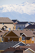 Rooftops of varying colors and size mimic the jagged peaks of the mountains in the distance.