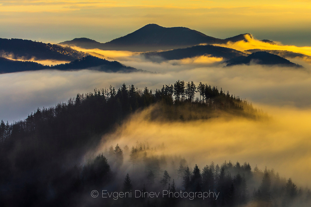 Layer of clouds movein over mountain hills at sunrise time