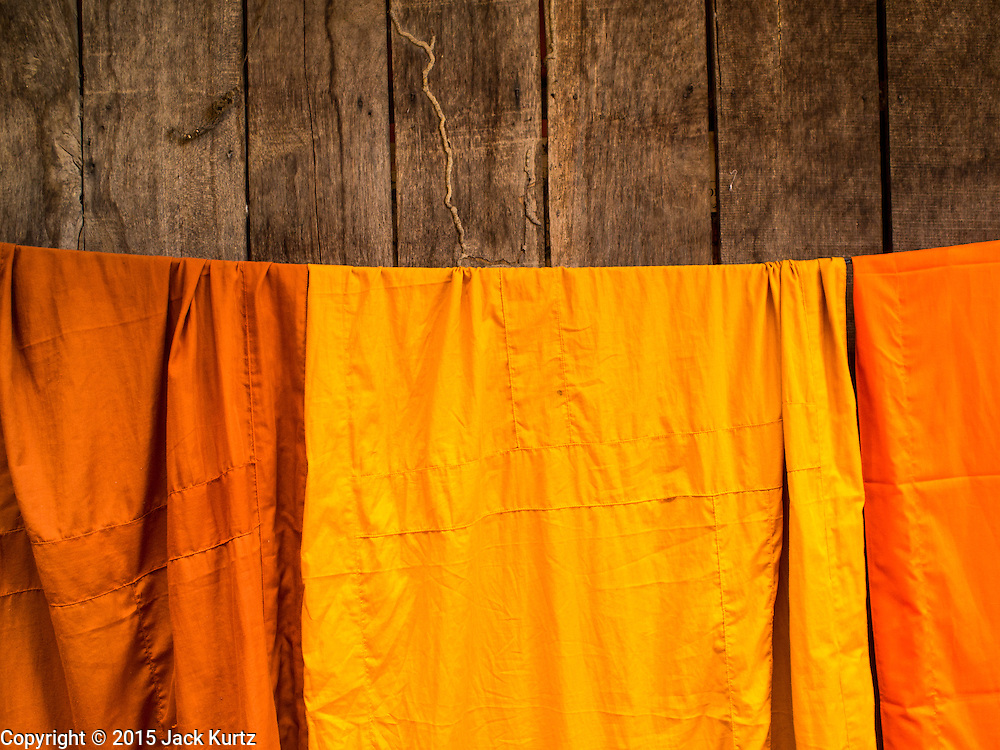 15 MARCH 2015 - SIEM REAP, SIEM REAP, CAMBODIA: Monks' robes hang to dry after being laundered at Wat Bo in Siem Reap. More than 1,200 Buddhist monks, from across Siem Reap province, received alms from Buddhist lay people during the morning long ceremony. Wat Bo was originally built to be a the temple for Siamese (Thai) troops when Siem Reap and western Cambodia were controlled by Siam (Thailand). Now Wat Bo is one of the most important temples in Siem Reap.      PHOTO BY JACK KURTZ