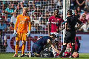 Marko Arnautovic (West Ham) receives treatment as Kasper Schmeichel (GK) (Capt) (Leicester City) looks on and Lee Probert (Referee) and Michail Antonio (West Ham) talk together during the Premier League match between West Ham United and Leicester City at the London Stadium, London, England on 20 April 2019.