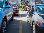 "LIAM MATTES, 7, reaches with his palm branch for the car parked next to his during a drive through Palm Sunday service sponsored by Luther Memorial Church on the campus of Grand View University in Des Moines. About 150 people attended the service. They remained in their cars while the ministers read a short passage from the Bible, handed out palms and blessed them. On Sunday, 05 April, Iowa reported 868 confirmed cases of the Novel Coronavirus (SARS-CoV-2) and COVID-19. There have been 22 deaths attributed to COVID-19 in Iowa. Restaurants, bars, movie theaters, places that draw crowds are closed until 30 April. The Governor has not ordered ""shelter in place"" but several Mayors, including the Mayor of Des Moines, have asked residents to stay in their homes for all but essential needs. People are being encouraged to practice ""social distancing"" and many businesses are requiring or encouraging employees to telecommute."
