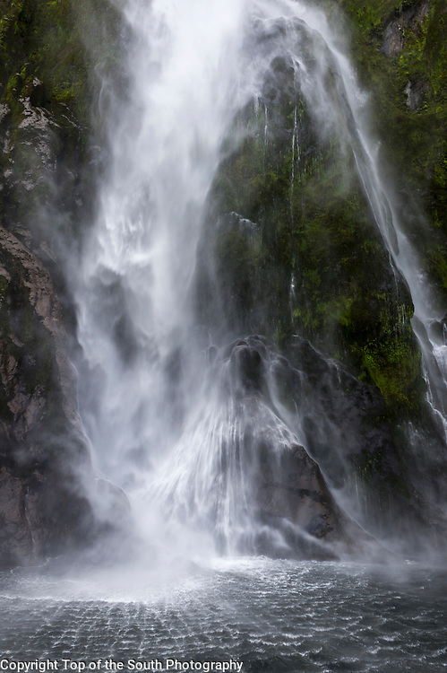 The 155 m Stirling Falls were named after the captain of the HMS Clio.<br /> Fiordland National Park, South Island, New Zealand.<br /> Geographical features...<br /> During the cooler past, glaciers carved many deep fiords, the most famous (and most visited) of which is Milford Sound. Other notable fiords include Doubtful Sound and Dusky Sound. From one of the peaks within Fiordland National Park, a view of Mount Aspiring/Tititea to the far north can be observed.<br />  Fiordland's coast is steep and crenellated, with the fiords running from the valleys of the southern ranges of the Southern Alps, such as the Kepler and Murchison Mountains. At the northern end of the park, several peaks rise to over 2,000 metres.<br />  Ice has carved islands from the mainland, leaving two large uninhabited offshore islands, Secretary Island and Resolution Island. Several large lakes lie wholly or partly within the park's boundaries, notably Lake Te Anau, Lake Manapouri, Lake Monowai, Lake Hauroko, and Lake Poteriteri. The Sutherland Falls, to the southwest of Milford Sound on the Milford Track, are among the world's highest waterfalls.<br />  Prevailing westerly winds blow moist air from the Tasman Sea onto the mountains; the cooling of this air as it rises produces a prodigious amount of rainfall, exceeding seven metres in many parts of the park. This supports the lush temperate rain forests of the Fiordland temperate forests ecoregion.