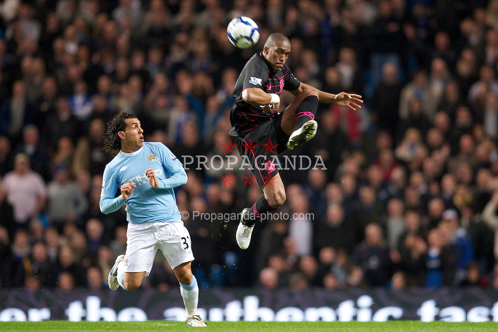 MANCHESTER, ENGLAND - Wednesday, March 24, 2010: Everton's Sylvain Distin and Manchester City's Carlos Tevez during the Premiership match at the City of Manchester Stadium. (Photo by David Rawcliffe/Propaganda)