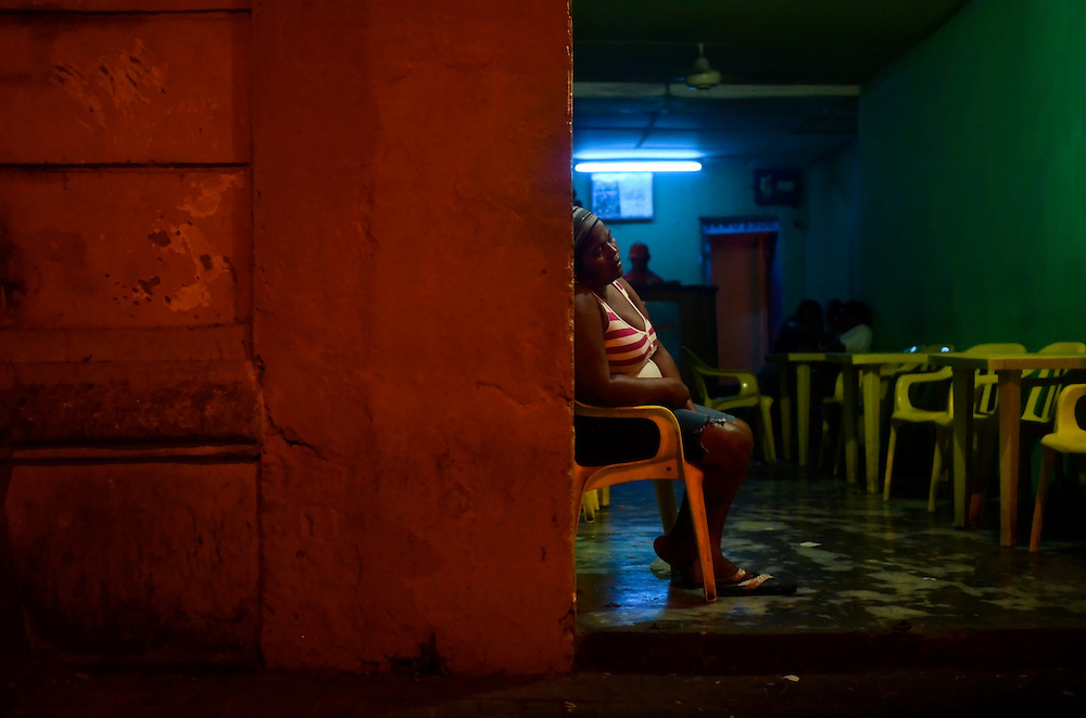 A woman sits at the entrance of a brothel in Cartagena, Colombia. This coastal city boasts many bars and discotecs where patrons can drink, dance, and pick up prostitutes. A sex scandal erupted recently when secret service agents were found bringing prostitutes to their hotel rooms while in Cartagena preparing for President Barack Obama's arrival to the Summit of the Americas.