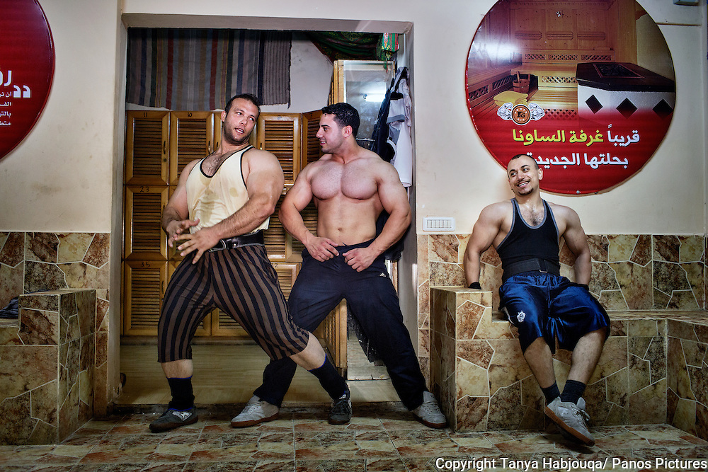 Gazan body builders jovially strike poses after a workout.