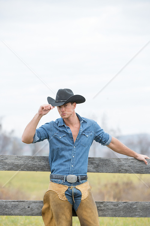 Portrait of a sexy All American cowboy All American cowboy in chaps leaning against a rustic wooden fence on a ranch