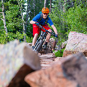 Andrew Whiteford rides through a technical boulder rock section of singletrack near Jackson, Wyoming.