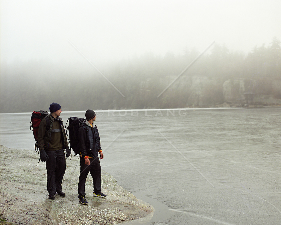 two men with backpacks standing near a frozen lake on a foggy day