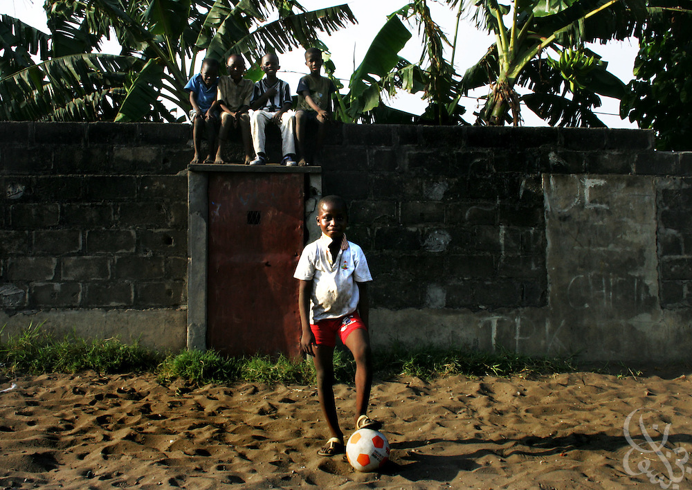 An Ivorian boy poses for a photo in the Koomassi neighborhood of Abidjan, Côte d'Ivoire February 17, 2006.  Most Ivorian boys dream of becoming national team members, or perhaps European club players, and football is an integral part of the social fabric of the Côte d'Ivoire.