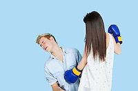 Young female boxer punching man over blue background