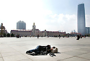 A traveler takes a nap in front of the Tianjin train station.