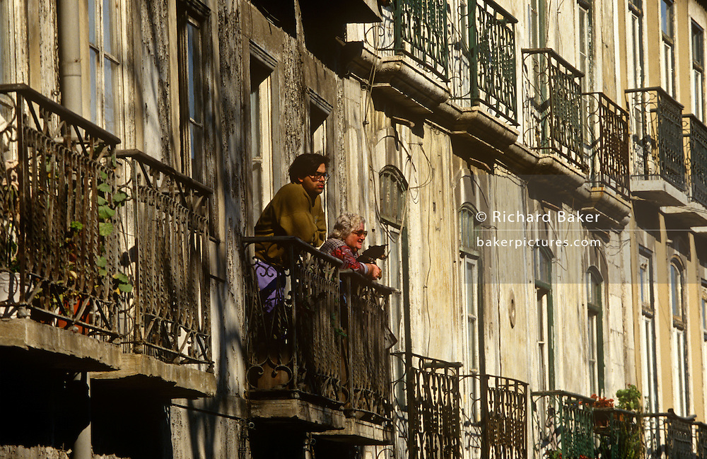 Locals look at street life below from the crumbling balconies of their old apartment block in Lisbon's Biarro Alto district.