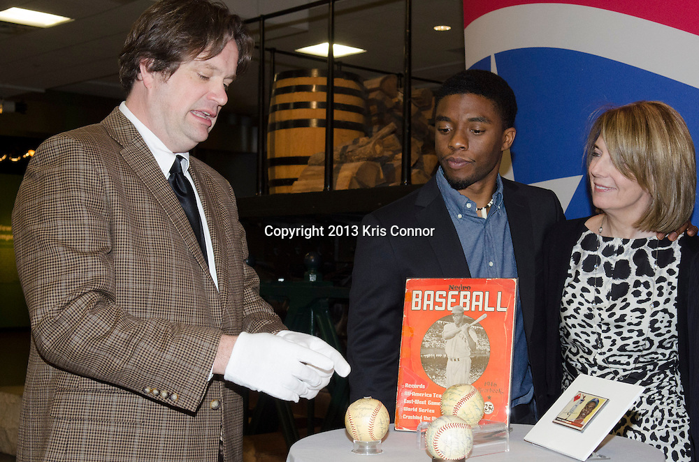 "WASHINGTON, DC - APRIL 15:  Chadwick Boseman, Carol Melton, Executive Vice President for Global Public Policy of Time Warner Inc,  John Gray, Director of the Smithsonian Museum of American History, and Lonnie G. Bunch III,  director of the Smithsonian's National Museum of African American History and Culture  pose with Jackie Robinson artifacts during the Washington DC screening of Warner Bro's film ""42"" at Smithsonian Museum of American History on April 15th, 2013. Guests included star of the film Chadwick Boseman, John Gray, Carol Melton, and Lonnie Bunch. Photo by Kris Connor/Warner Bros"