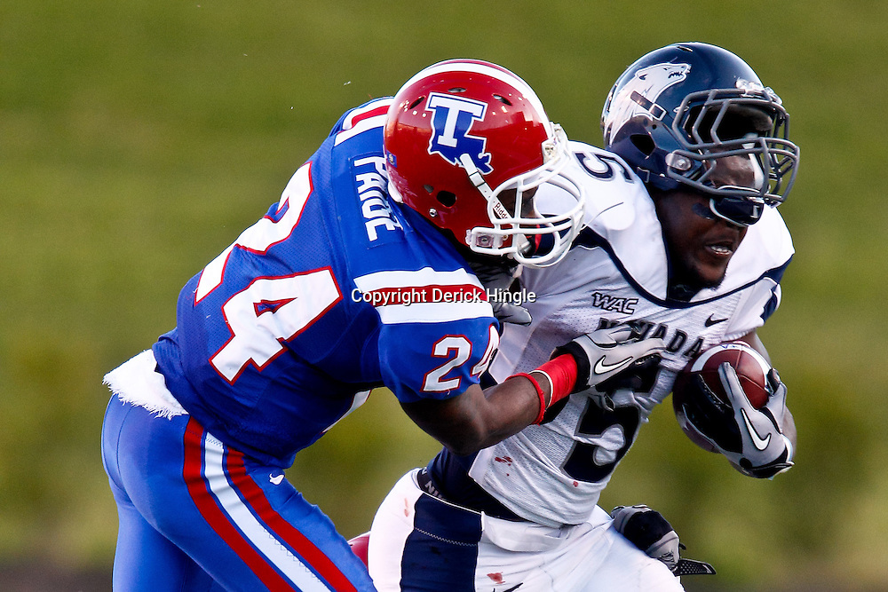 December 4, 2010; Ruston, LA, USA;  Nevada Wolf Pack running back Mike Ball (5) loses his helmet as he is hit by Louisiana Tech Bulldogs cornerback Olajuwon Paige (24) during the second half at Joe Aillet Stadium.  Nevada defeated Louisiana Tech 35-17. Mandatory Credit: Derick E. Hingle