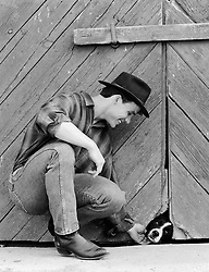 man petting a dog who is peaking his head through a hole in a barn doorway