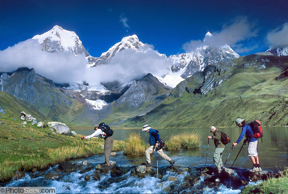"""Trekkers cross the outlet stream of Lake Carhuacocha (13,600 feet) in the Cordillera Huayhuash, Andes Mountains, Peru, South America. On the left, Yerupaja Grande (east face, 6635 m or 21,770 ft) is the second-highest peak in Peru, highest in Cordillera Huayhuash, and highest point in the Amazon River watershed. At center is Yerupaja Chico (20,080 feet). On right is Mount Jirishanca (""""Icy Beak of the Hummingbird,"""" 6126 m or 20,098 feet). Published in the following: 1) on the cover and inside of """"Climbs and Treks in the Cordillera Huayhuash of Peru"""" guidebook Copyright 2005 by Jeremy Frimer, ISBN #0-9733035-5-7, Elaho Publishing; 2) Wilderness Travel 2005, 2007, 2013 Catalog of Adventures, and 2009-2011 web client survey; 3) """"Fuentes, Conversacion y gramatica,"""" a Spanish textbook by Rusch, Houghton Mifflin Company/Cengage Learning in 2004, 2011, 2013; 4) image for SteriPEN package, a handheld water purifier made by Hydro-Photon, Inc. of Blue Hill, Maine, 2007; 5) """"Skills in Global Geography"""" Cambridge University Press, Australia textbook 2007; 6) Swedish trekking company site www.adventurelovers.se; 7) """"Light Travel: Photography on the Go"""" book by Tom Dempsey 2009, 2010."""