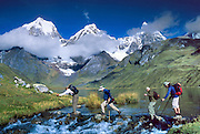 "Trekkers cross the outlet stream of Lake Carhuacocha (13,600 feet) in the Cordillera Huayhuash, Andes Mountains, Peru, South America. On the left, Yerupaja Grande (east face, 6635 m or 21,770 ft) is the second-highest peak in Peru, highest in Cordillera Huayhuash, and highest point in the Amazon River watershed. At center is Yerupaja Chico (20,080 feet). On right is Mount Jirishanca (""Icy Beak of the Hummingbird,"" 6126 m or 20,098 feet). Published in the following: 1) on the cover and inside of ""Climbs and Treks in the Cordillera Huayhuash of Peru"" guidebook Copyright 2005 by Jeremy Frimer, ISBN #0-9733035-5-7, Elaho Publishing; 2) Wilderness Travel 2005, 2007, 2013 Catalog of Adventures, and 2009-2011 web client survey; 3) ""Fuentes, Conversacion y gramatica,"" a Spanish textbook by Rusch, Houghton Mifflin Company/Cengage Learning in 2004, 2011, 2013; 4) image for SteriPEN package, a handheld water purifier made by Hydro-Photon, Inc. of Blue Hill, Maine, 2007; 5) ""Skills in Global Geography"" Cambridge University Press, Australia textbook 2007; 6) Swedish trekking company site www.adventurelovers.se; 7) ""Light Travel: Photography on the Go"" book by Tom Dempsey 2009, 2010."