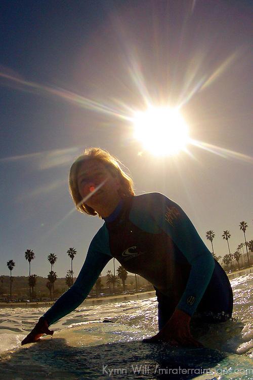 USA, California, La Jolla. Woman heading out to surf at La Jolla Shores in San Diego.