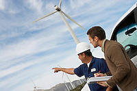 Engineers examining wind turbines by car at wind farm