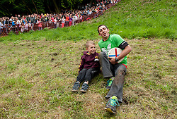 © Licensed to London News Pictures. 25/05/2015. Brockworth, Gloucestershire, UK.  Chris Anderson with his son Ryley Anderson aged 5 from Brockworth after Chris wins the first mens' race at the annual traditional Cheese Rolling races, which by custom take place on Bank Holiday Monday.  Chris has won 14 Cheese Rolling races over the years.  Participants race down the very steep Coopers Hill chasing a Double Gloucester Cheese, and injuries sometimes happen. Photo credit : Simon Chapman/LNP