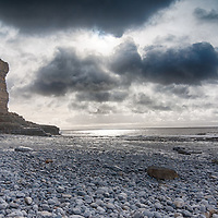 storm brewing over sea with rocky beach and cliffs