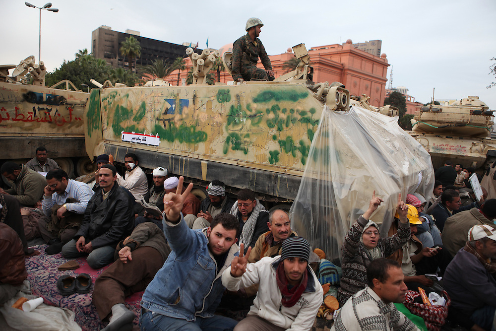 """On """"Sunday of the martyrs"""" at Tahrir Square, Egyptian pro-democracy protesters sit in front of an army tank to prevent it from leaving or further entering the square."""