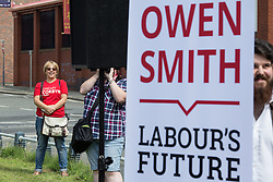 © Licensed to London News Pictures . 30/07/2016 . Liverpool , UK . Jeremy Corbyn campaigner watches an Owen Smith rally in a field off Bridgewater Street in Liverpool after the booked venue , the Camp and Furnace warehouse , reportedly cancelled the booking . Smith is campaigning to replace Jeremy Corbyn as the leader of the Labour Party . Photo credit : Joel Goodman/LNP