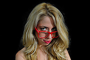 Intelligent blond woman with red glasses on black background