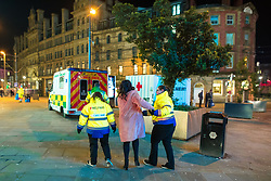 """© Licensed to London News Pictures . 16/12/2017. Manchester, UK. A woman is assisted by welfare workers in to a """" welfare unit """", offering people tea, coffee and medical support, that is placed alongside an ambulance , on the pavement opposite the Printworks nightclub venue . Revellers out in Manchester City Centre overnight during """" Mad Friday """" , named for historically being one of the busiest nights of the year for the emergency services in the UK . Photo credit: Joel Goodman/LNP"""