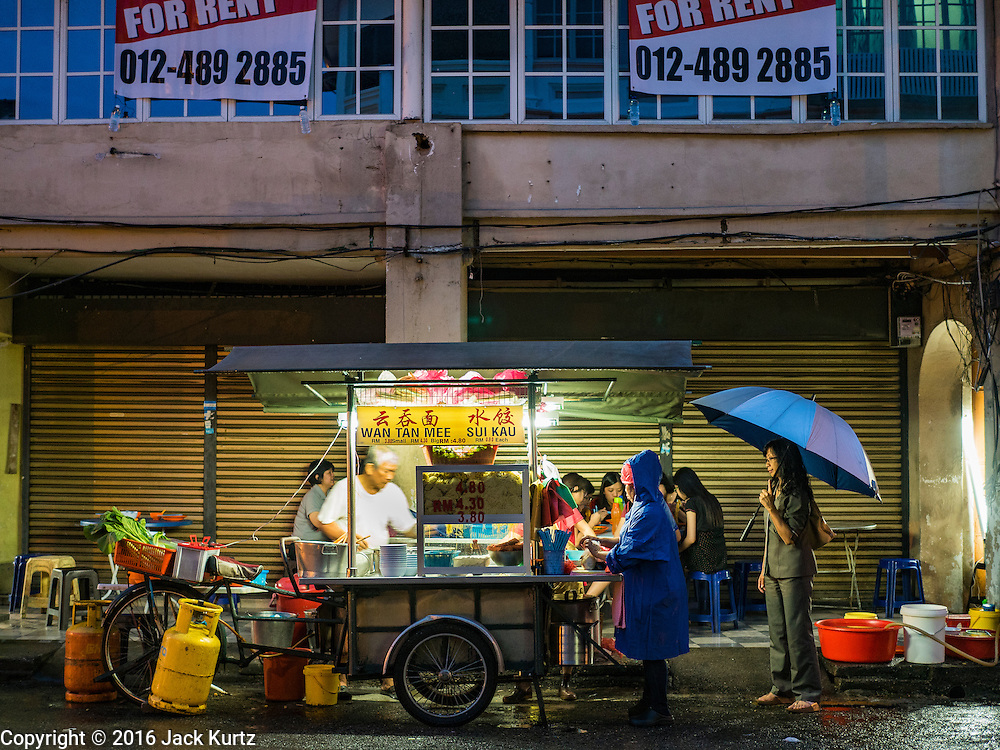 15 NOVEMBER 2016 - GEORGE TOWN, PENANG, MALAYSIA:  A street food vendor sells noodles from his cart in George Town, Penang. George Town is a UNESCO World Heritage city and wrestles with maintaining its traditional lifestyle and mass tourism.           PHOTO BY JACK KURTZ