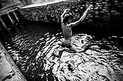 27th September, 2014, Mehrauli, India. A boy leaps into the Gandhak Ki Baoli in Mehrauli,on the 27th September, 2014, Delhi, India<br /> <br /> At the turn of the last century, Delhi had more than 100 baolis, today, many of them have caved in or dried up owing to the declining water table. The number has shrunk to about 15, according to the ASI (Acheological Survey of India). Stepwells (Baolis) are examples of the many types of storage and irrigation tanks that were developed in India, mainly to cope with seasonal fluctuations in water availability. <br /> <br /> PHOTOGRAPH BY AND COPYRIGHT OF SIMON DE TREY-WHITE<br /> <br /> + 91 98103 99809<br /> + 91 11 435 06980<br /> +44 07966 405896<br /> +44 1963 220 745<br /> email: simon@simondetreywhite.com