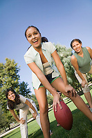 Three women playing football outdoors.