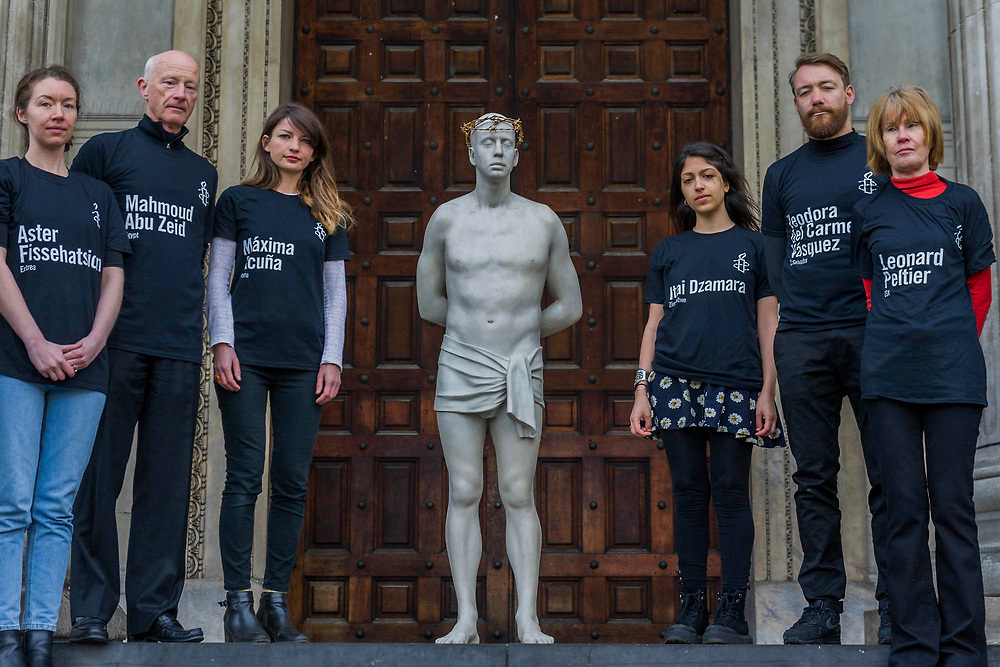 """Amnesty staff with victims names on their t-shirts - Kate Allen, Director of Amnesty International UK, helped by Canon Mark Oakley (Chancellor of St Paul's Cathedral), installs Mark Wallinger's 'Ecce Homo' statue at St Paul's Cathedral. The life-size sculpture shows the figure of Jesus Christ and was the first artwork to be shown on Trafalgar Square's fourth plinth in 1999.Mark Wallinger, who won the Turner Prize in 2007, said: """"This vulnerable figure will stand at the top of the steps outside the entrance to St Paul's Cathedral as we approach Easter to highlight the plight of people around the world who are imprisoned and whose lives are threatened for speaking the truth, and for what they believe."""""""