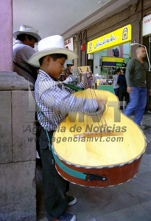 Toluca, Méx.- No importa que sea mas grande el bandolón que el artista cuando se necesita ganar algunas monedas en los Portales de Toluca. Agencia MVT / Mario B. Arciniega