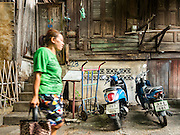 07 APRIL 2016 - BANGKOK, THAILAND: A woman walks past a 200 year old home in Mahakan Fort. The home, one of the original homes in the squatters' community in the fort, was built without nails using a wedging technique. The concrete base was added a few years ago. Mahakan Fort was built in 1783 during the reign of Siamese King Rama I. It was one of 14 fortresses designed to protect Bangkok from foreign invaders, and only of two remaining, the others have been torn down. A community developed in the fort when people started building houses and moving into it during the reign of King Rama V (1868-1910). The land was expropriated by Bangkok city government in 1992, but the people living in the fort refused to move. In 2004 courts ruled against the residents and said the city could take the land. The final eviction notices were posted last week and the residents given until April 30 to move out. After that their homes, some of which are nearly 200 years old, will be destroyed.       PHOTO BY JACK KURTZ